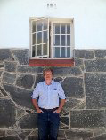 John Dear standing under the open window of Mandela's prison cell, Robben Island, Jan. 23, 2014