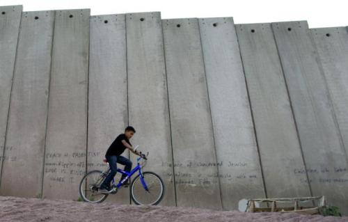 A Palestinian youth rides his bicycle next to Israel's apartheid wall on the outskirts of Jerusalem.