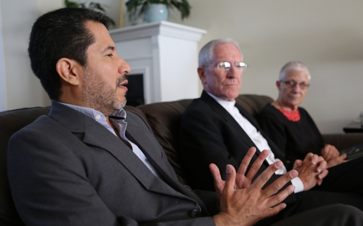 Jose Henriquez gestures during an interview in Washington Sept. 23. Looking on are Bishop Kevin Dowling and Marie Dennis. (CNS/Bob Roller)