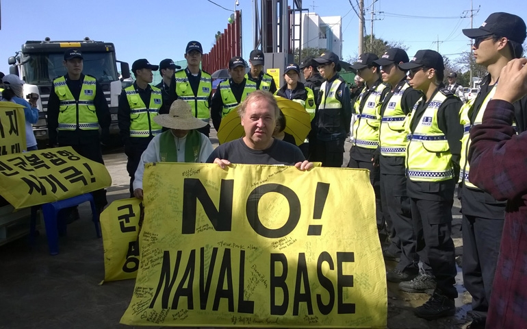 Police surround Art Laffin and other activists as they protest at the main entrance of a U.S.-backed Korean naval base on Jeju Island.