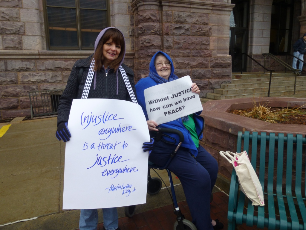 Pax Christi Southeastern South Dakota members Candace Grant and Mary Ann Garrigan witness against police brutality in front of the Federal Building on December 11, 2014.