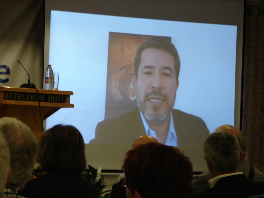 Pax Christi International Secretary General José Henríquez addresses the world assembly via Skype from Amman, Jordan after being denied entry into Israel.