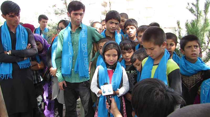 Sakina speaks to a T.V. reporter. Rohullah is on her right, Inam on her left.