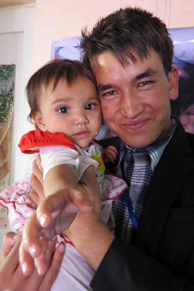 Ali, one of the Afghan Peace Volunteers who assisted the five Kunduz families, including the toddler named Rana in the photo.