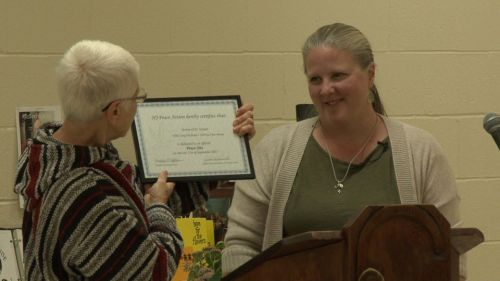 "Kathy O'Leary of Pax Christi New Jersey accepting a certificate from New Jersey Peace Action recognizing the Shrine of St. Joseph as an official ""peace site."""