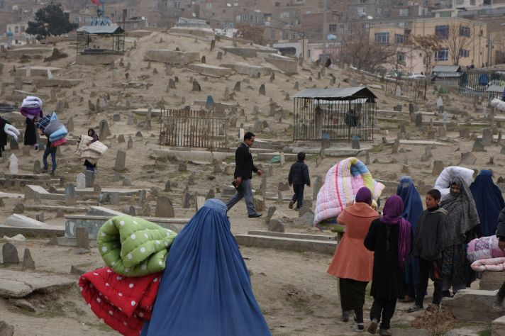 Bearing quilted bed covers, Afghans walk through the cemetery to their mountainside homes. Photo by Carolyn Coe